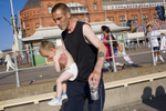 A father with his young son and a can of lager by the benches on Blackpool promenade. The city has been attracting holiday visitors ever since 1735, when the first guest house opened. In the 19th century, it became a popular working-class destination among the British.