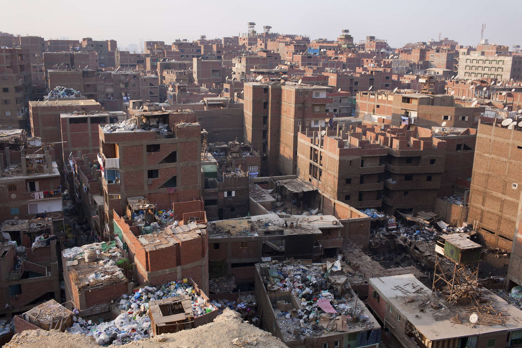 "A view across the Cairo suburb of Moqqatam, home to around 25,000 coptic ChristiansZabaleen, which literally means ""garbage collectors"" have assumed a semi-official role as Cairo's binmen. The Zabaleen men usually do two shifts. They leave at about four or five in the morning, and again at about nine. The poorer Zabaleen use donkey carts, but many earn enough to rent trucks. They then take the garbage back to their homes for the women to pick through for items to recycle."