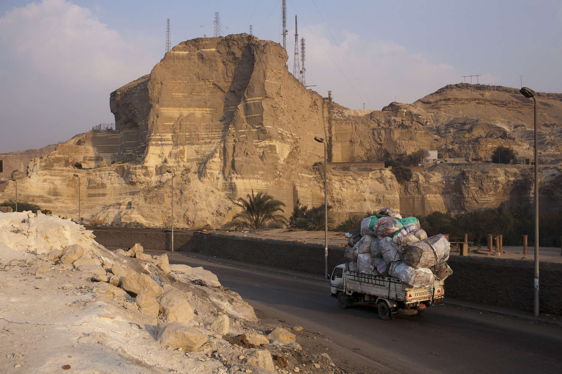 """A Zabaleen garbage collection truck returns to the Cairo suburb of Moqqatam at the end of a shift collecting trash from the cities streets and homes. Zabaleen, which literally means """"garbage collectors"""" have assumed a semi-official role as Cairo's binmen. The Zabaleen men usually do two shifts. They leave at about four or five in the morning, and again at about nine. The poorer Zabaleen use donkey carts, but many earn enough to rent trucks. They then take the garbage back to their homes for the women to pick through for items to recycle."""