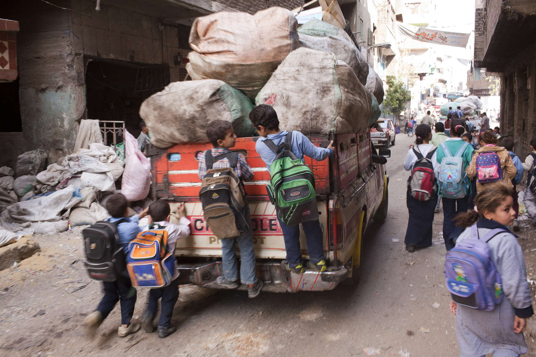 "Schoolchildren hitch a ride on the back of a garbage collection truck driving through the central street of Moqqatam.Moqqatam is a suburb on the edge of Cairo and home to a people known as the Zabaleen, said to be the world's greatest waste recyclers. The Zabaleen, which means plainly enough, ""the garbage collectors"", pick up around 4,000 tons of Cairo's waste each day. American researchers have shown that the Zabaleen recycle 85% of this garbage into something useful: a higher rate than anywhere else on the planet. The men do two shifts leaving about 4am and again around 9am. The rubbish is taken back to Moqqatam for the women to sit in and sort through. The organic waste is fed to livestock (the Zabaleen are originally swine herders), the rest sorted for recycling. The future of the Zabaleen is uncertain: if the Cairo authorities get their way, this community of around 25,000 Coptic Christians living in a Muslim country will be gone, and with it, their unique lifestyle."
