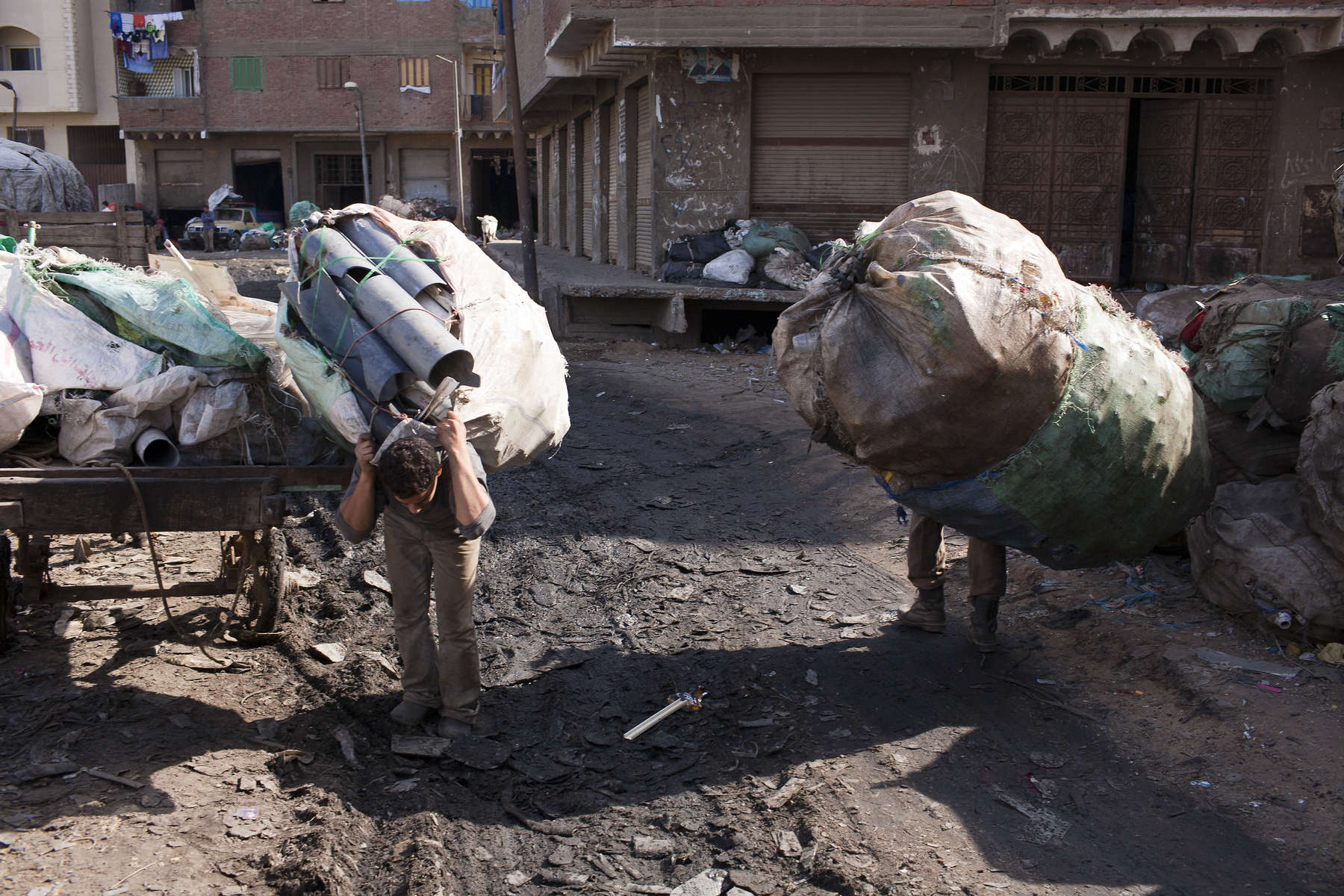 "Zabaleen carry recycled garbage through a street in Moqqatam.Moqqatam is a suburb on the edge of Cairo and home to a people known as the Zabaleen, said to be the world's greatest waste recyclers. The Zabaleen, which means plainly enough, ""the garbage collectors"", pick up around 4,000 tons of Cairo's waste each day. American researchers have shown that the Zabaleen recycle 85% of this garbage into something useful: a higher rate than anywhere else on the planet. The men do two shifts leaving about 4am and again around 9am. The rubbish is taken back to Moqqatam for the women to sit in and sort through. The organic waste is fed to livestock (the Zabaleen are originally swine herders), the rest sorted for recycling. The future of the Zabaleen is uncertain: if the Cairo authorities get their way, this community of around 25,000 Coptic Christians living in a Muslim country will be gone, and with it, their unique lifestyle."