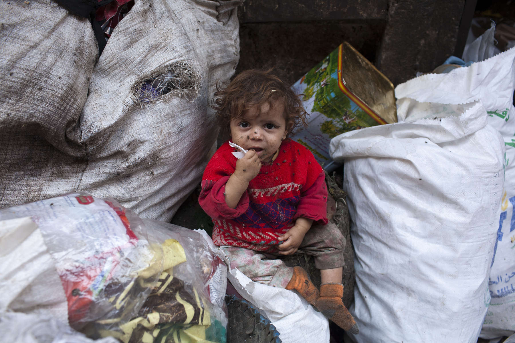 """A filthy young child sits on a pile of rubbish stacked on a street in Moqqatam.Moqqatam is a suburb on the edge of Cairo and home to a people known as the Zabaleen, said to be the world's greatest waste recyclers. The Zabaleen, which means plainly enough, """"the garbage collectors"""", pick up around 4,000 tons of Cairo's waste each day. American researchers have shown that the Zabaleen recycle 85% of this garbage into something useful: a higher rate than anywhere else on the planet. The men do two shifts leaving about 4am and again around 9am. The rubbish is taken back to Moqqatam for the women to sit in and sort through. The organic waste is fed to livestock (the Zabaleen are originally swine herders), the rest sorted for recycling. The future of the Zabaleen is uncertain: if the Cairo authorities get their way, this community of around 25,000 Coptic Christians living in a Muslim country will be gone, and with it, their unique lifestyle."""