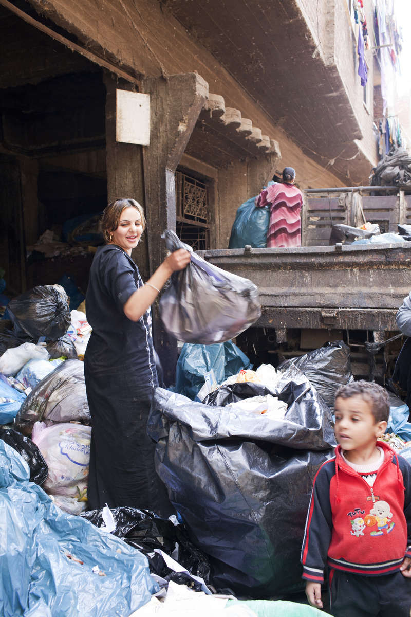 "A young Zabaleen woman sorts through garbage collected from Cairo for useful items to recycle.Moqqatam is a suburb on the edge of Cairo and home to a people known as the Zabaleen, said to be the world's greatest waste recyclers. The Zabaleen, which means plainly enough, ""the garbage collectors"", pick up around 4,000 tons of Cairo's waste each day. American researchers have shown that the Zabaleen recycle 85% of this garbage into something useful: a higher rate than anywhere else on the planet. The men do two shifts leaving about 4am and again around 9am. The rubbish is taken back to Moqqatam for the women to sit in and sort through. The organic waste is fed to livestock (the Zabaleen are originally swine herders), the rest sorted for recycling. The future of the Zabaleen is uncertain: if the Cairo authorities get their way, this community of around 25,000 Coptic Christians living in a Muslim country will be gone, and with it, their unique lifestyle."