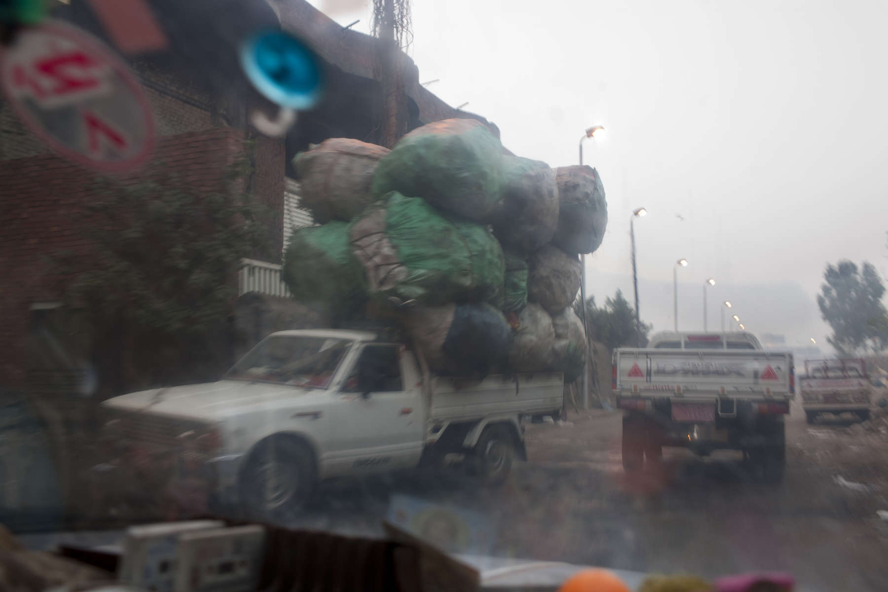 "A truck heads out from Moqqatam on a morning shift to collect garbage.Moqqatam is a suburb on the edge of Cairo and home to a people known as the Zabaleen, said to be the world's greatest waste recyclers. The Zabaleen, which means plainly enough, ""the garbage collectors"", pick up around 4,000 tons of Cairo's waste each day. American researchers have shown that the Zabaleen recycle 85% of this garbage into something useful: a higher rate than anywhere else on the planet. The men do two shifts leaving about 4am and again around 9am. The rubbish is taken back to Moqqatam for the women to sit in and sort through. The organic waste is fed to livestock (the Zabaleen are originally swine herders), the rest sorted for recycling. The future of the Zabaleen is uncertain: if the Cairo authorities get their way, this community of around 25,000 Coptic Christians living in a Muslim country will be gone, and with it, their unique lifestyle."
