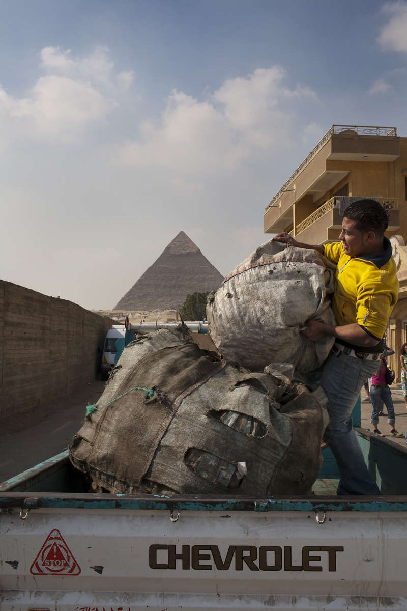 "Walid, a young Zabaleen man, collects garbage from the streets in front of the pyramids in Cairo. Zabaleen, which literally means ""garbage collectors"" have assumed a semi-official role as Cairo's binmen. The Zabaleen men usually do two shifts. They leave at about four or five in the morning, and again at about nine. The poorer Zabaleen use donkey carts, but many earn enough to rent trucks. They then take the garbage back to their homes for the women to sort through for items to recycle."