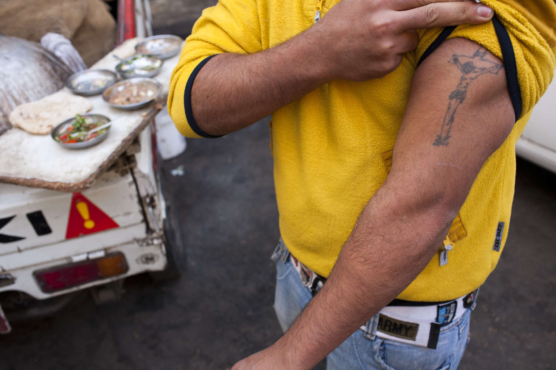 "Walid, a young Zabaleen man, shows his tattoo of Jesus Christ on the cross. The Zabaleen are a community of around 25, 000 Coptic Christians living in the Cairo uburb of Moqqatam.Zabaleen, which literally means ""garbage collectors"" have assumed a semi-official role as Cairo's binmen. The Zabaleen men usually do two shifts. They leave at about four or five in the morning, and again at about nine. The poorer Zabaleen use donkey carts, but many earn enough to rent trucks. They then take the garbage back to their homes for the women to pick through for items to recycle."