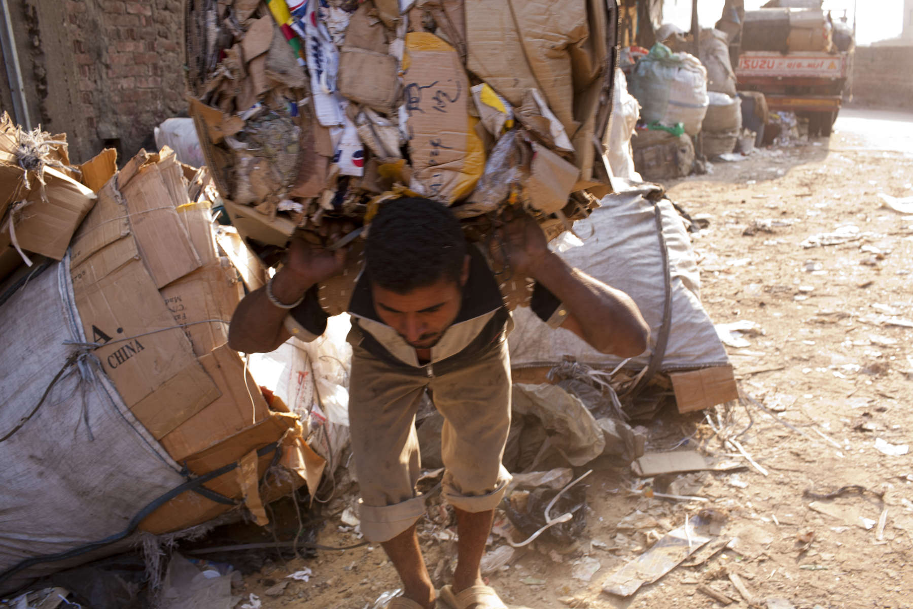 "A Zabaleen man hauls a load of cardboard for recycling through a dusty street in Moqqatam.Moqqatam is a suburb on the edge of Cairo and home to a people known as the Zabaleen, said to be the world's greatest waste recyclers. The Zabaleen, which means plainly enough, ""the garbage collectors"", pick up around 4,000 tons of Cairo's waste each day. American researchers have shown that the Zabaleen recycle 85% of this garbage into something useful: a higher rate than anywhere else on the planet. The men do two shifts leaving about 4am and again around 9am. The rubbish is taken back to Moqqatam for the women to sit in and sort through. The organic waste is fed to livestock (the Zabaleen are originally swine herders), the rest sorted for recycling. The future of the Zabaleen is uncertain: if the Cairo authorities get their way, this community of around 25,000 Coptic Christians living in a Muslim country will be gone, and with it, their unique lifestyle."