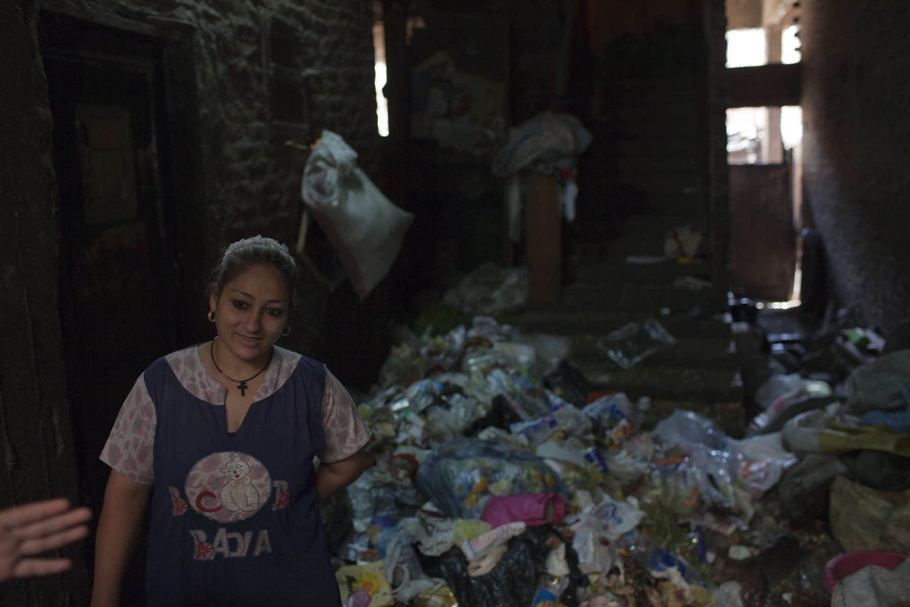 "A woman in the ground floor of her home in Moqqatam prepares to sort through garbage for useful items to recycle.Moqqatam is a suburb on the edge of Cairo and home to a people known as the Zabaleen, said to be the world's greatest waste recyclers. The Zabaleen, which means plainly enough, ""the garbage collectors"", pick up around 4,000 tons of Cairo's waste each day. American researchers have shown that the Zabaleen recycle 85% of this garbage into something useful: a higher rate than anywhere else on the planet. The men do two shifts leaving about 4am and again around 9am. The rubbish is taken back to Moqqatam for the women to sit in and sort through. The organic waste is fed to livestock (the Zabaleen are originally swine herders), the rest sorted for recycling. The future of the Zabaleen is uncertain: if the Cairo authorities get their way, this community of around 25,000 Coptic Christians living in a Muslim country will be gone, and with it, their unique lifestyle."