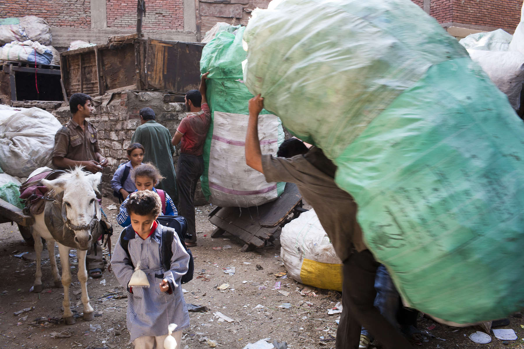 "Zabaleen children make their way to lessons through the tightly packed streets of Moqqatam.Moqqatam is a suburb on the edge of Cairo and home to a people known as the Zabaleen, said to be the world's greatest waste recyclers. The Zabaleen, which means plainly enough, ""the garbage collectors"", pick up around 4,000 tons of Cairo's waste each day. American researchers have shown that the Zabaleen recycle 85% of this garbage into something useful: a higher rate than anywhere else on the planet. The men do two shifts leaving about 4am and again around 9am. The rubbish is taken back to Moqqatam for the women to sit in and sort through. The organic waste is fed to livestock (the Zabaleen are originally swine herders), the rest sorted for recycling. The future of the Zabaleen is uncertain: if the Cairo authorities get their way, this community of around 25,000 Coptic Christians living in a Muslim country will be gone, and with it, their unique lifestyle."