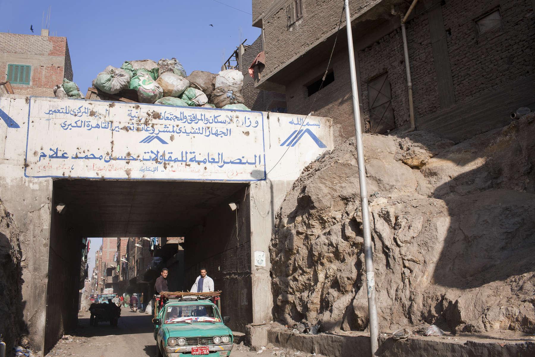 "The gate to the Cairo suburb of MoqqatamMoqqatam is on the edge of Cairo and home to a people known as the Zabaleen, said to be the world's greatest waste recyclers. The Zabaleen, which means plainly enough, ""the garbage collectors"", pick up around 4,000 tons of Cairo's waste each day. American researchers have shown that the Zabaleen recycle 85% of this garbage into something useful: a higher rate than anywhere else on the planet. The men do two shifts leaving about 4am and again around 9am. The rubbish is taken back to Moqqatam for the women to sit in and sort through. The organic waste is fed to livestock (the Zabaleen are originally swine herders), the rest sorted for recycling. The future of the Zabaleen is uncertain: if the Cairo authorities get their way, this community of around 25,000 Coptic Christians living in a Muslim country will be gone, and with it, their unique lifestyle."