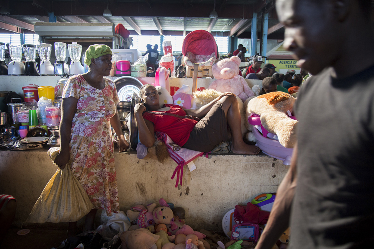 A Haitian woman rests surrounded by the stuffed animals that she sells at the market in the Dominican border town of Dajabon. She purchases merchandise from the nearby town of Cap Haitian that comes in on ships from Miami.