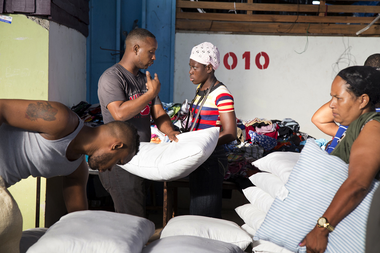 A Haitian woman sells pillows to a Dominican man at the market in the Dominican border town of Dajabon. Many Haitians buy used merchandise in the nearby town of Cap Haitan that arrives on ships from Miami to sell at this market.
