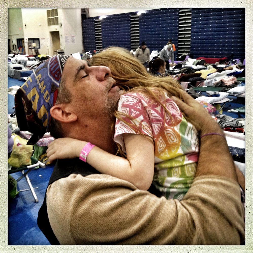 Tom's River, NJ | November 4, 2012 A displaced resident of Seaside Heights, John holds his daughter tightly in the Tom's River High School gymnasium, which housed many who lost their homes in the first week following hurricane Sandy's destructive visit to New Jersey.