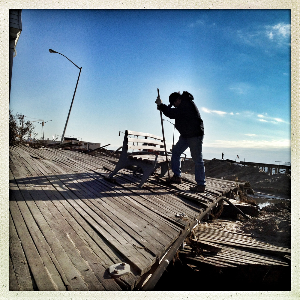 "Rockaway Beach, NY | November 5, 2012 Bill Louw uses a long piece of rebar to rip a tightly fastened bench from a slab of boardwalk that landed in his neighbors from yard. ""I've lived in the Rockaways my entire life. I was born in that house two doors behind me. My mother still lives there, and I live around the corner. They are just going to throw this out… I think it'll look great in my back yard… A memory from Sandy."""