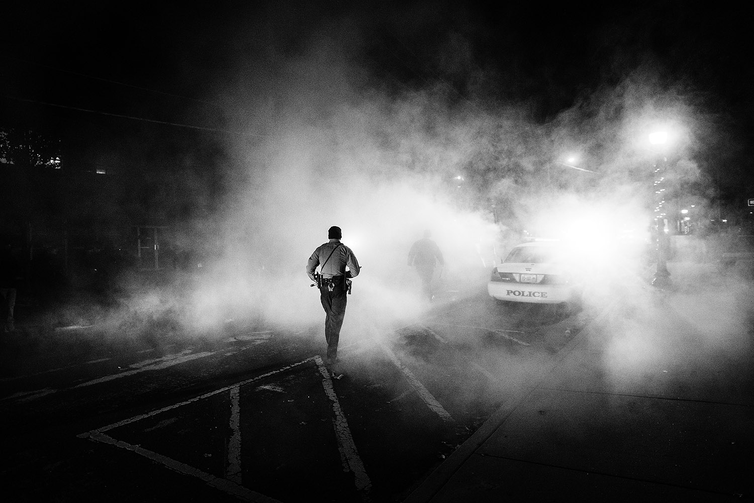 FERGUSON, MO - NOVEMBER 25: A police officer wades into a cloud of smoke as numerous police respond to the destruction of a police car parked outside the Ferguson City Hall. Angered protesters marched past downtown Ferguson a night after the riots and destruction followed the announcement of the grand jury's decision not to indict white police officer Darren Wilson in the death of unarmed black teen Michael Brown. (Photo by Benjamin Lowy/Reportage by Getty Images)