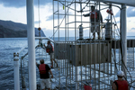 Isla Guadalupe, Mexico - November 10, 2015: The ship's crew and dive masters prepare to submerge the massive steel dive cages off the aft of the Belle Amis. The ship is capable of sending down three separate cages that hold one dive master and three divers to a depth of 30-40 feet every 45 minutes. The are also two surface cages - one at 6 feet and the other at 18 feet. All are fed by compressed surface air, with divers only needing to use a rebreather and a weighted belt to hold them down as the cages submerge. (Photograph by Benjamin Lowy for The New York Times)