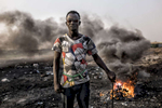 Agbogbloshie, Ghana | December 18, 2015Yaro, the self-styled leader of a band of migrant teens, poses in front of the copper burning grounds in the Agbogbloshie dump site. His pants are held up by a frayed jump rope, and his {quote}Freakish{quote} t-shit was printed with cigarette boxes and ironic phrase {quote}You are going to die anyways.{quote} Yaro and his gang are part of a distinct pecking order in the dump - where men and teens burn the plastic, rubber and metal off of manufactured parts made of copper. First there are the buyers of the waste, men who cart in used computers, automobiles and any other junk they can get their hands on. In turn this manufactured garbage is sold to small {quote}storefronts{quote} in the dump that distribute it to the younger men to burn. Below that strata of employment are the boys that walk through the debris fields picking up the copper remains hoping to collect enough to fill a kilo bag. The resulting raw copper is sold back to construction and mineral component wholesalers, which reintroduce the recycled copper back into the world market. Once a wetland suburb of Accra, Agbogbloshie is home to a vast dumping ground - once labeled the world's largest e-waste site - that covers an unstable swamp, the garbage and soot a carpet that sways with every step, sometimes swallowing new migrants who arrived hoping to make a slim income to feed themselves each day.
