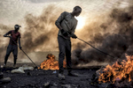 Agbogbloshie, Ghana   December 18, 2015Two teens burn the plastic and rubber off of copper wiring, which they plan to resell, in the e-waste dump of Agbogbloshie. Once a wetland suburb of Accra, the area is home to a vast dumping ground and slum that stretches as far as the eye can see. Once labeled the world's largest e-waste site - though since disputed - it is a hell on earth for poor migrant workers who toil in its toxic landscape - separating refuse from reusable metals - hoping to make a slim income to feed themselves each day.