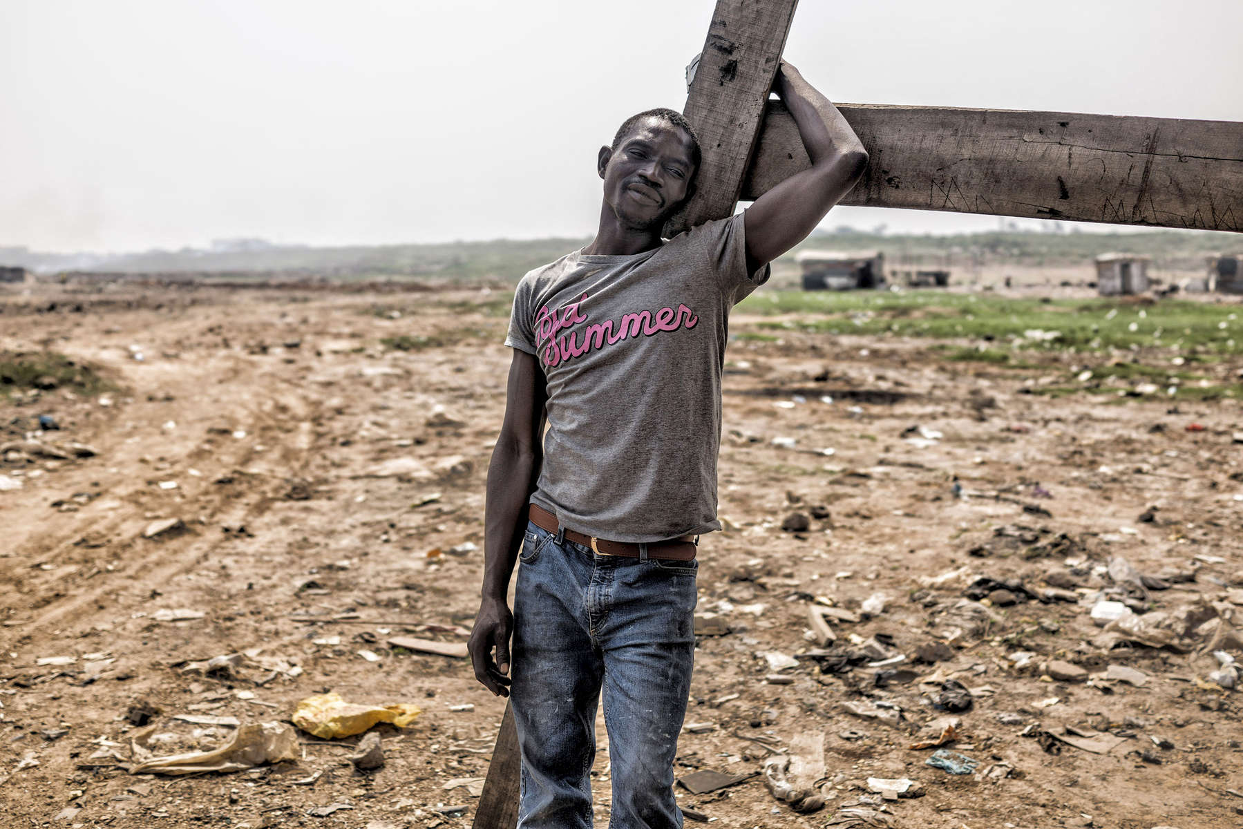 Hassan Hussein - who has lived in the Agbogbloshie dump for 14 years - leans on a small wooden housing frame that litters the dump site. The Agbogbloshie dump's burning fields - where young men - almost all internal migrants from Ghana's northern Tamale region - toil in toxic smoke, burning down manufactured parts into their basic copper components hoping to make a slim income to feed themselves each day.
