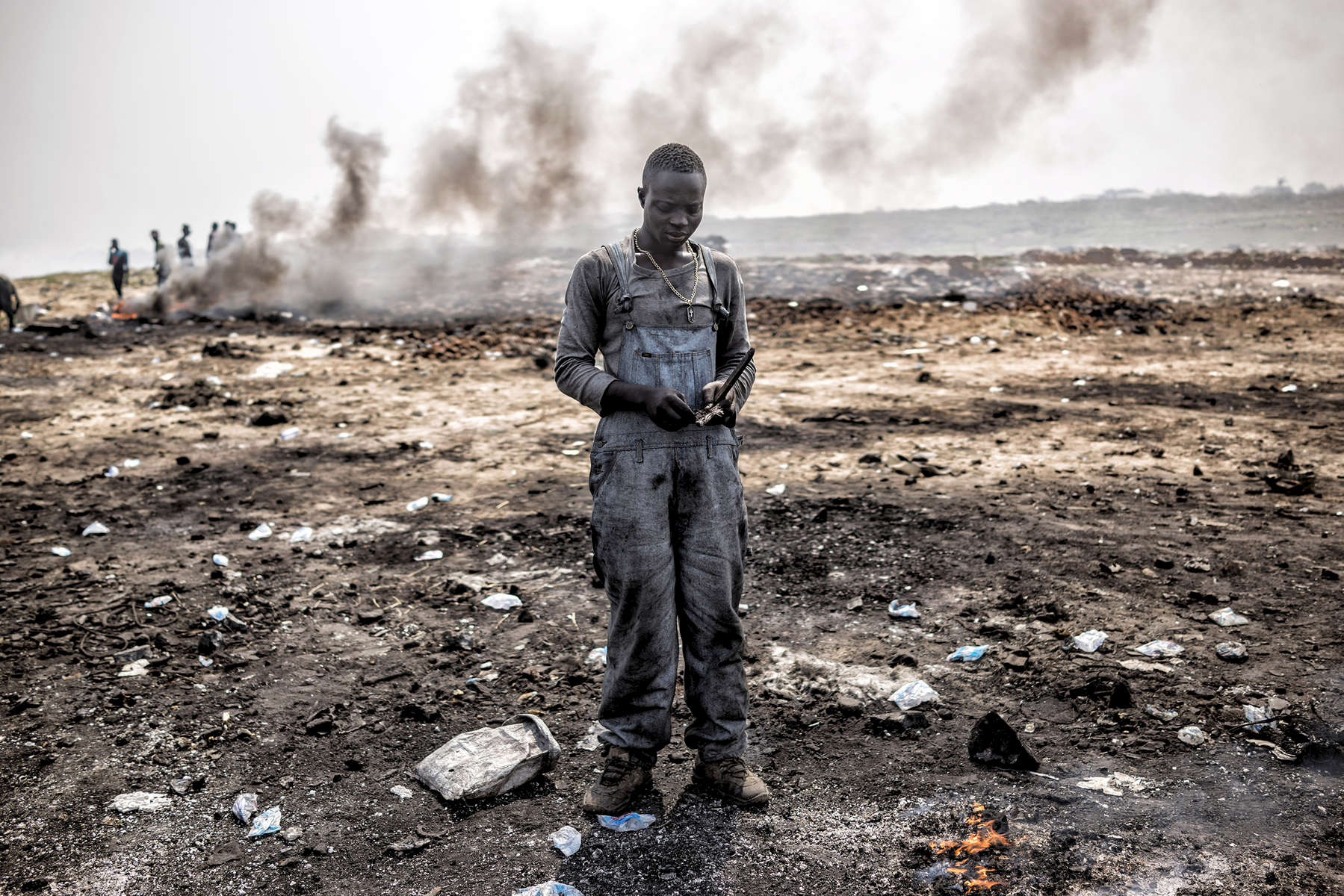 Agbogbloshie, Ghana | December 19, 2015Ernest looks for raw copper among the Agbogbloshie dump's burning fields - where young men - almost all internal migrants from Ghana's northern Tamale region - toil in toxic smoke, burning down manufactured parts into their basic copper components. The dump works with a specific process. First there are the buyers of the waste, men who cart in used computers, automobiles and any other junk they can get their hands on. In turn this manufactured garbage is sold to small {quote}storefronts{quote} in the dump that distribute it to the younger men to burn. Below that strata of employment are the boys that walk through the debris fields picking up the copper remains hoping to collect enough to fill a kilo bag. The resulting raw copper is sold back to construction and mineral component wholesalers, which reintroduce the recycled copper back into the world market. A wetland suburb of Accra, Agbogbloshie is home to a vast dumping ground - once labeled the world's largest e-waste site - that covers an unstable swamp, the garbage and soot a carpet that sways with every step, sometimes swallowing new migrants who arrived hoping to make a slim income to feed themselves each day.