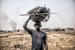 benlowyAgbogbloshie, Ghana | December 19, 2015Yakub, 17, carries a jumble of computer wires, a few alternators and several automobile starters in a makeshift bowl on his head. All these parts are destined to the Agbogbloshie burn sites, where young men - almost all internal migrants from Ghana's northern Tamale region - toil in toxic smoke, burning down manufactured parts into their basic copper components. A wetland suburb of Accra, Agbogbloshie is home to a vast dumping ground - once labeled the world's largest e-waste site - that covers an unstable swamp, the garbage and soot a carpet that sways with every step, sometimes swallowing new migrants who arrived hoping to make a slim income to feed themselves each day.