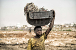 Agbogbloshie, Ghana | December 19, 2015Yakubu Tanko carries the shell of a TV filled with computer and electrical wires on his head. All these parts are destined to the Agbogbloshie burn sites, where young men - almost all internal migrants from Ghana's northern Tamale region - toil in toxic smoke, burning down manufactured parts into their basic copper components. The dump works with a specific process. First there are the buyers of the waste, men who cart in used computers, automobiles and any other junk they can get their hands on. In turn this manufactured garbage is sold to small {quote}storefronts{quote} in the dump that distribute it to the younger men to burn. Below that strata of employment are the boys that walk through the debris fields picking up the copper remains hoping to collect enough to fill a kilo bag. The resulting raw copper is sold back to construction and mineral component wholesalers, which reintroduce the recycled copper back into the world market. A wetland suburb of Accra, Agbogbloshie is home to a vast dumping ground - once labeled the world's largest e-waste site - that covers an unstable swamp, the garbage and soot a carpet that sways with every step, sometimes swallowing new migrants who arrived hoping to make a slim income to feed themselves each day.