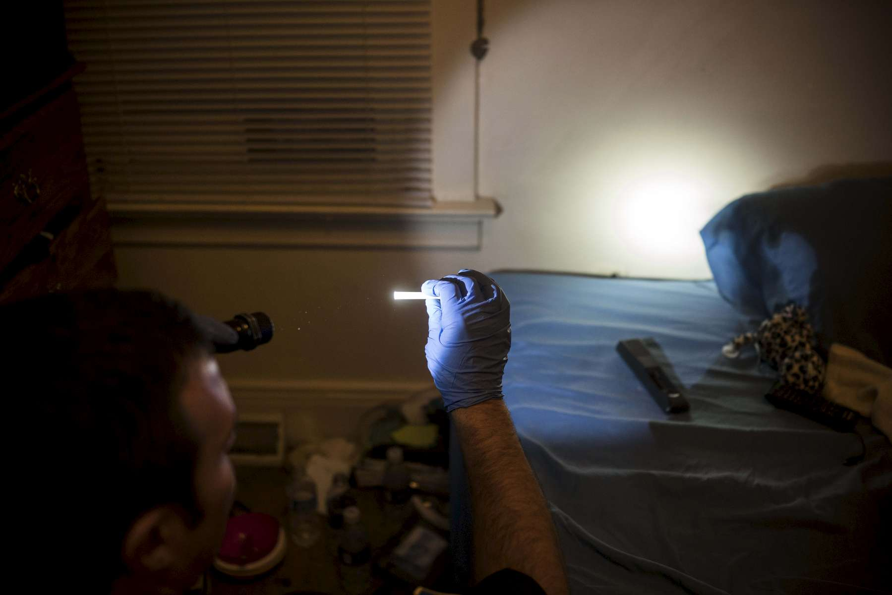 """East Liverpool, OH - October 8, 2016: An East Liverpool police officer holds up a drug pipe after searching through a teenager's room. The teen's mother called the police after her daughter vandalized her car. She asked and invited the police officer into her home, to search her daughters room and take out whatever drugs he found. She said """"Im tired of her using and I don't know what to do about it…. Just take it all.."""" The officer went into the girls room, searching for drug paraphernalia - pipes, bottle caps filled with water, burnt and missing spoons (the mother complained that all her spoons were missing) even ratchets from a ratchet set used to drain heroine into syringes. """"Don't touch anything in this room without gloves,"""" said the officer, """"the phetenol can kill you… [but] you are enabling your daughter by letting her come back and living here."""""""