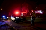 East Liverpool, OH - October 8, 2016: Crystal, a known drug user stands handcuffed in front of police cars, but was allowed to smoke a cigarette as the police search the car she was a passenger in for illicit drugs. East Liverpool is such a small community, with police and addicts often knowing each other their whole lives, small curtsies are ofter afforded to each.