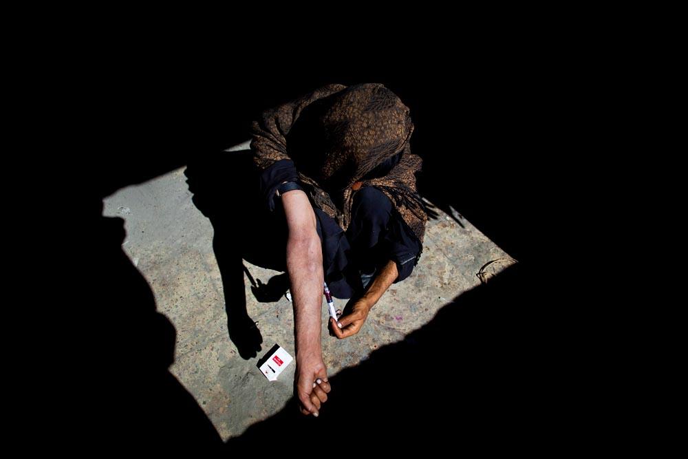 An addict shoots heroin.