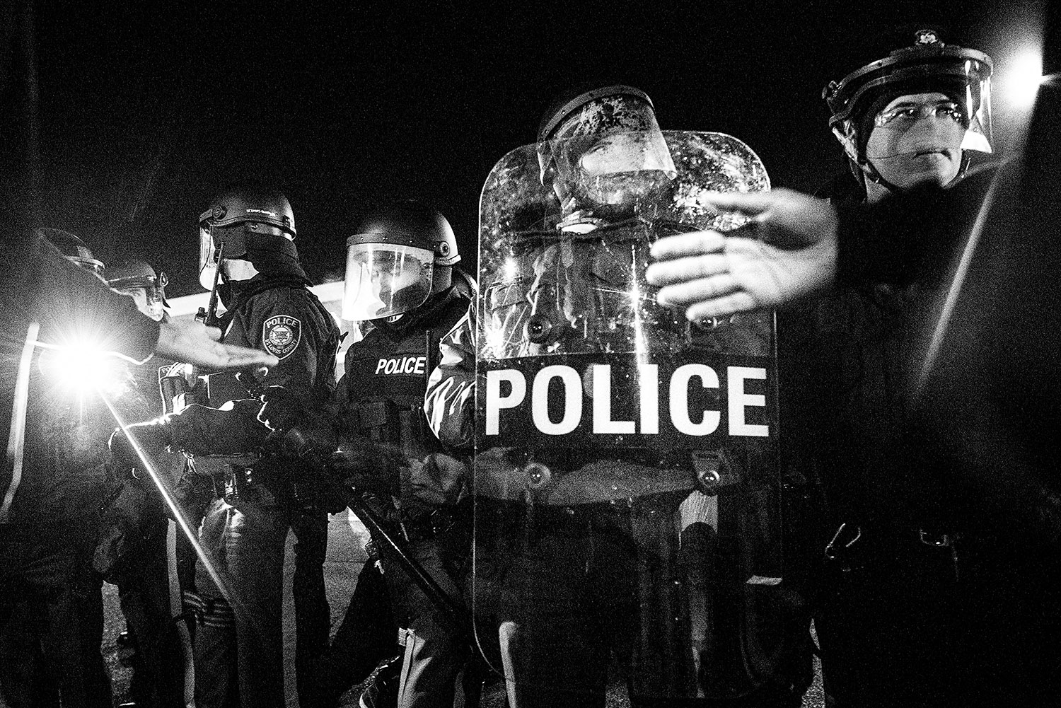 FERGUSON, MO - NOVEMBER 25: Protesters and police interact, sometimes violently, in front of the Ferguson police department after a night or riots and destruction following the grand jury's decision not to indict police officer Darren Wilson in the death of teen Michael Brown. The Ferguson police were criticized for their heavy handed and violent tactics following the protests and riots that were sparked by the killing of unarmed black teen Michael Brown by white police officer Darren Wilson in August 2014. (Photo by Benjamin Lowy/Reportage by Getty Images)