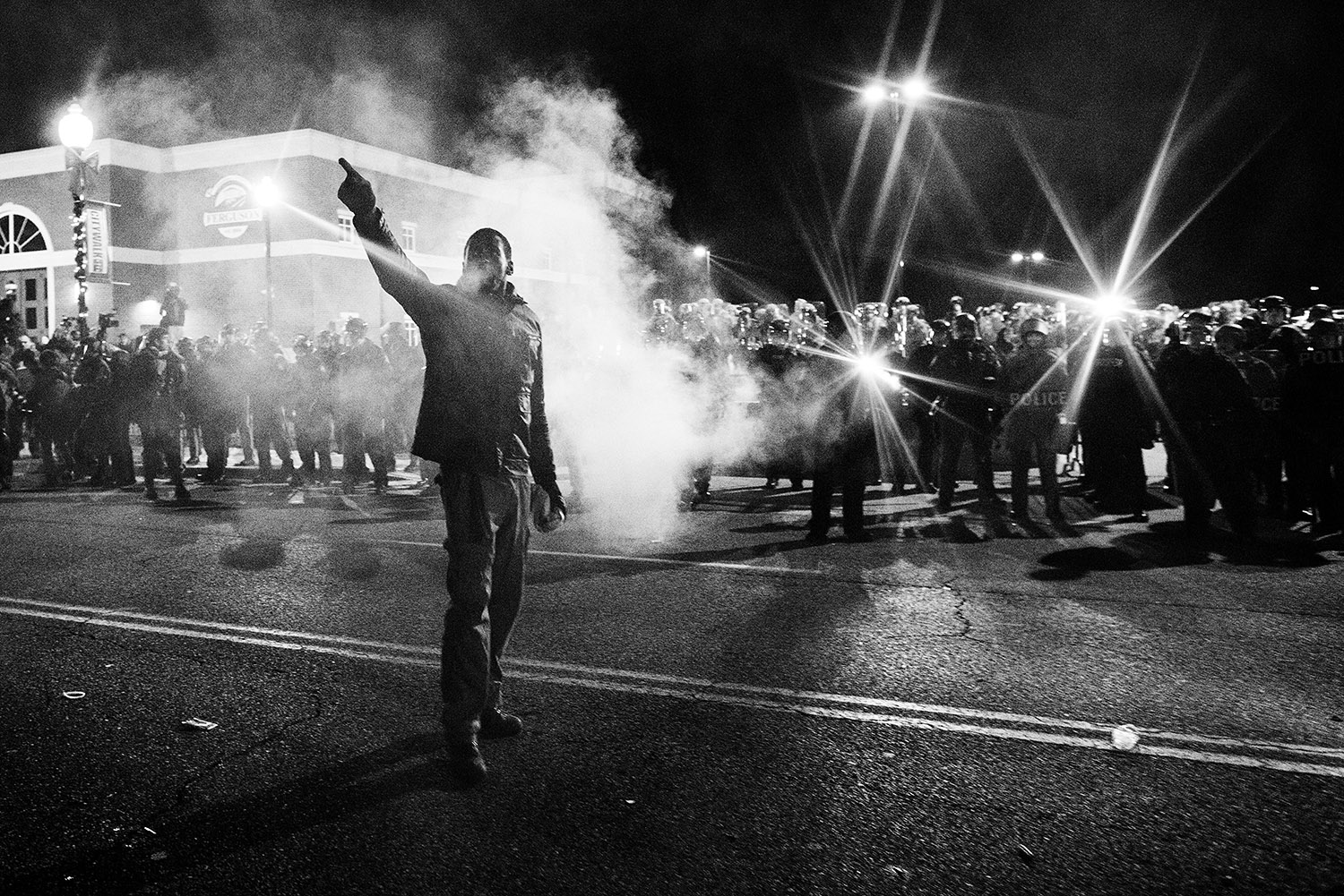 FERGUSON, MO - NOVEMBER 25: A protester points out the origin of a smoke bomb thrown at the police and national guard formations protecting the Ferguson police department, the night after riots rocked the suburb following the announcement of the grand jury's decision not to indict white police officer Darren Wilson in the death of unarmed black teen Michael Brown. Many protesters sought to deescalate violent confrontations with the police. (Photo by Benjamin Lowy/Reportage by Getty Images)