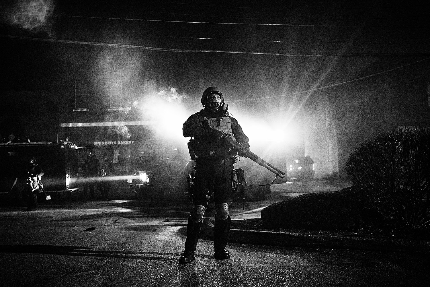 FERGUSON, MO - NOVEMBER 25: A riot police officer wades into a cloud of tear gas as numerous police units respond to the destruction of a police car parked outside the Ferguson City Hall. Angered protesters marched past downtown Ferguson a night after the riots and destruction followed the announcement of the grand jury's decision not to indict white police officer Darren Wilson in the death of unarmed black teen Michael Brown. (Photo by Benjamin Lowy/Reportage by Getty Images)