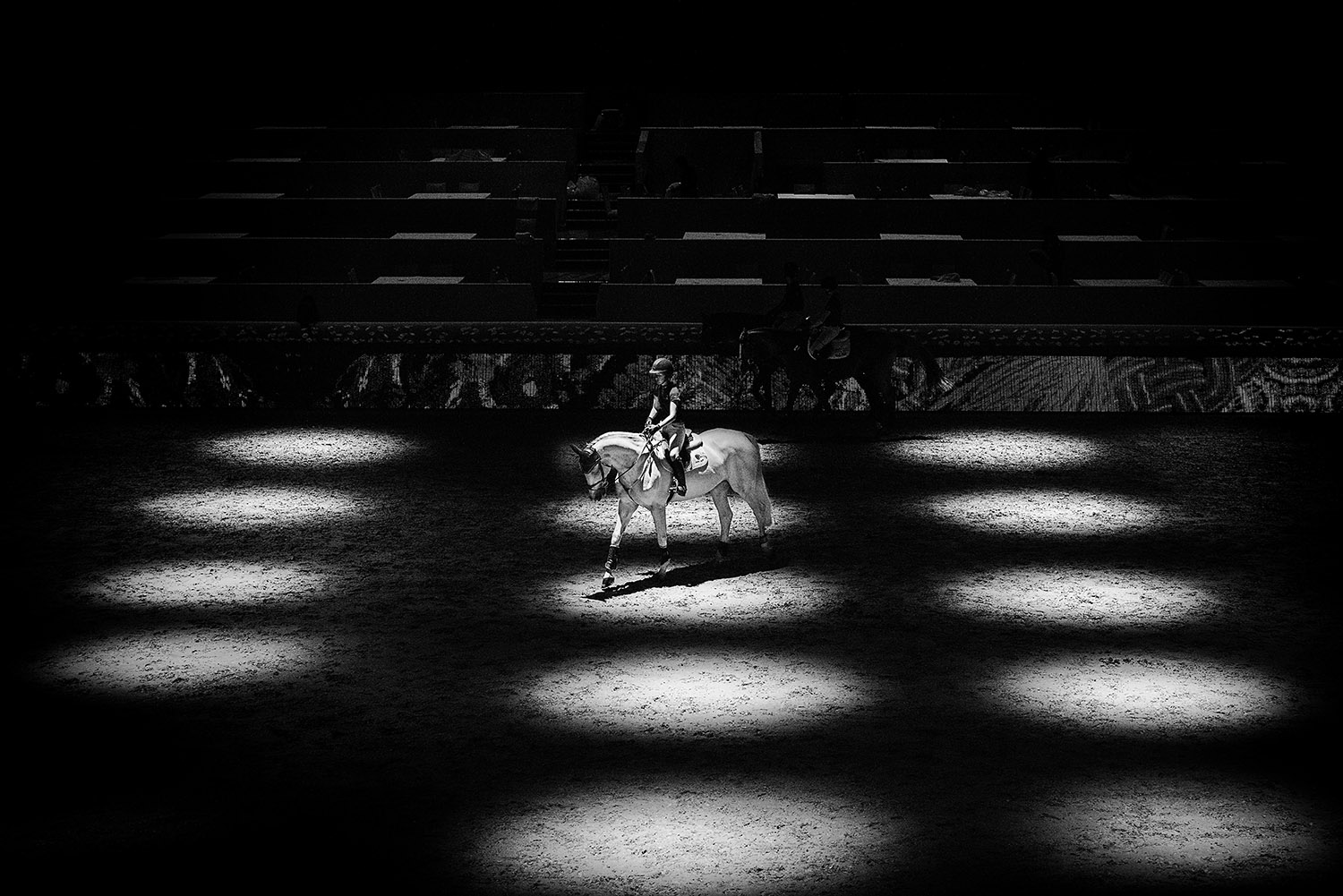 LOS ANGELES, CA - SEPTEMBER 24: Upon arrival to the competition, a rider warms up her horse in the ring and tries to acclimate the horse to its surroundings -- most notably the ad-filled LED perimeter screen, which can prove distracting. {quote}The LED doesn't move ... it might scare the horses,{quote} says event director Matthieu Gheysen. {quote}We do not move the ads for the 75 seconds when the rider is actually jumping.{quote}(Photo by Benjamin Lowy/Reportage by Getty Images)