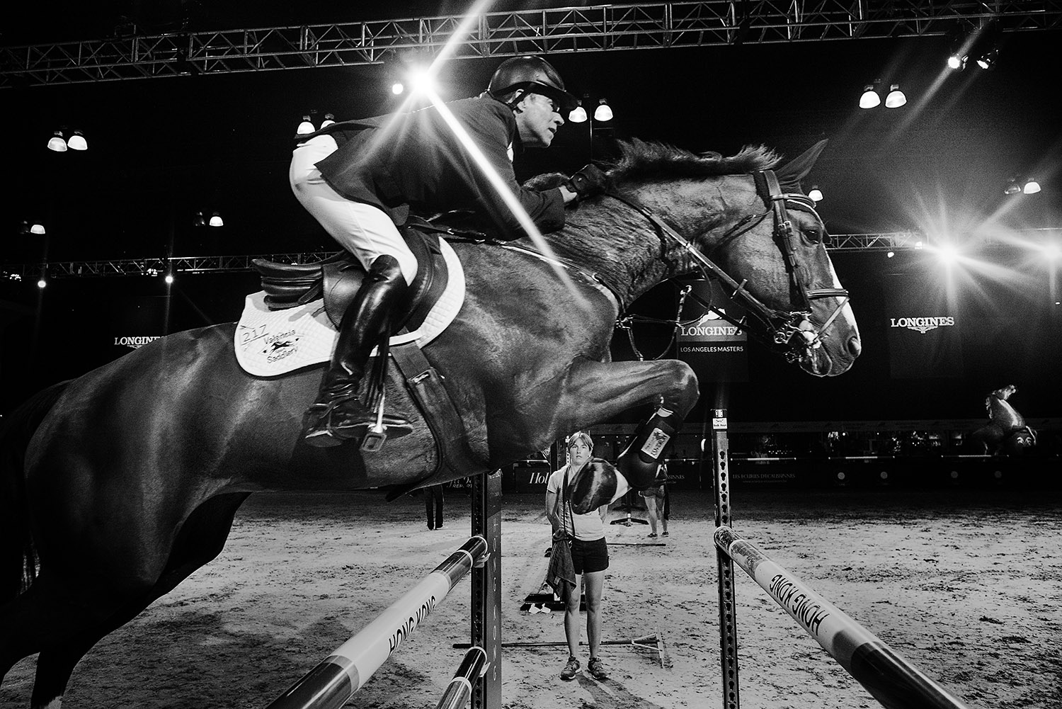 LOS ANGELES, CA - SEPTEMBER 25: A horse and its rider leap over an obstacle in the LA Convention center paddock during the LA Masters Grand Slam.
