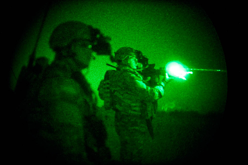 A US soldier, using a gun-mounted infrared targeting laser, marks a landing zone for incoming troop transport helicopters. The soldiers had successfully carried out an air assault, raiding over 30 targeted areas in a large rural area near Iskanderiyah.