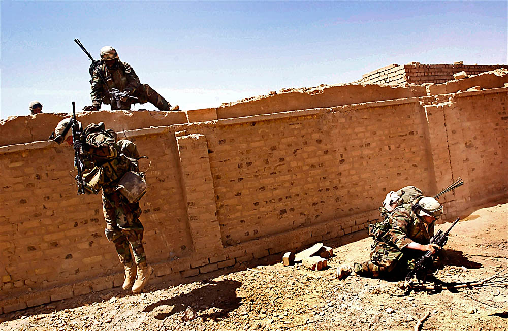While under fire, US soldiers scale a crumbling brick wall during an assault in Najaf.