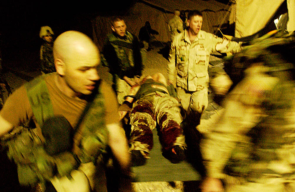 Immediately following a grenade attack on their commander's tent, soldiers of the 101st Airborne carry away one of the wounded from the scene. The attack was carried out by Sergeant Hasan Akbar of the 326th Engineer Battalion injured 14 soldiers and killed 2.