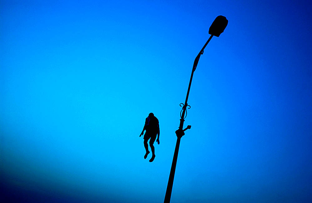 An Iraqi man launches himself off a lamppost on the Al Shuhada Bridge and into the Tigris River on a hot Baghdad night.