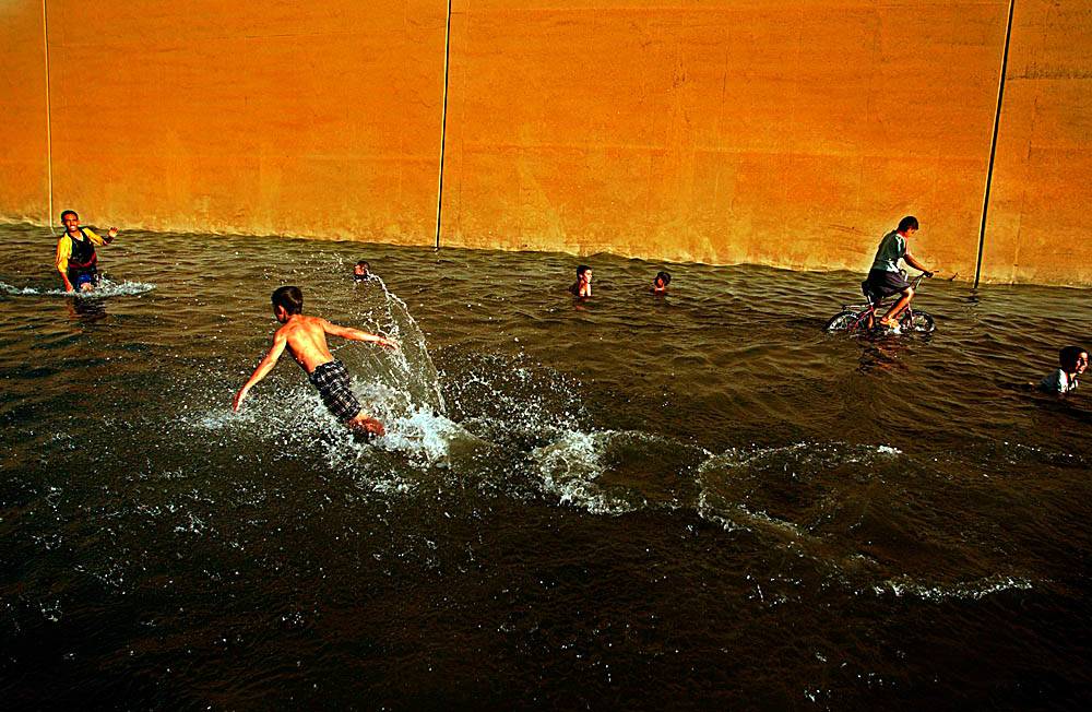 Children play in an abandoned underpass submerged under thousands of gallons of water after a water main in the Baghdad suburb of Adyhamia became the target of saboteurs.