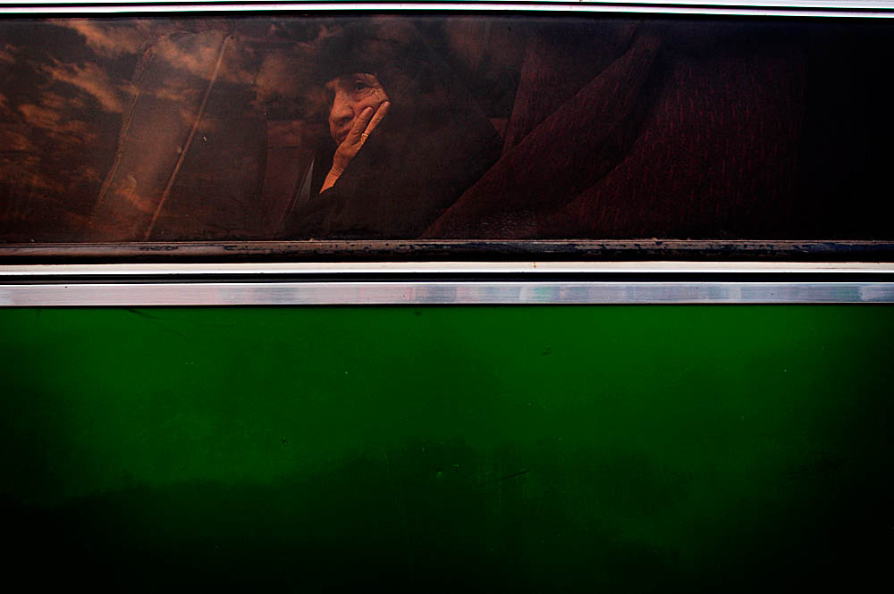 A Kurdish woman on her way to the Hadj looks out a chartered bus window following a massive car bomb explosion nearby.