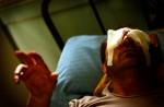 A blinded Iraqi man man reaches out for help as he is treated in a Baghdad hospital following a car bombing.