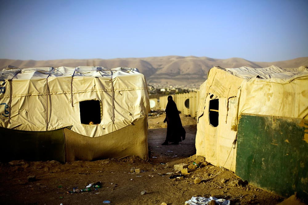 A woman walk through an Arab refugee camp in Kurdistan.