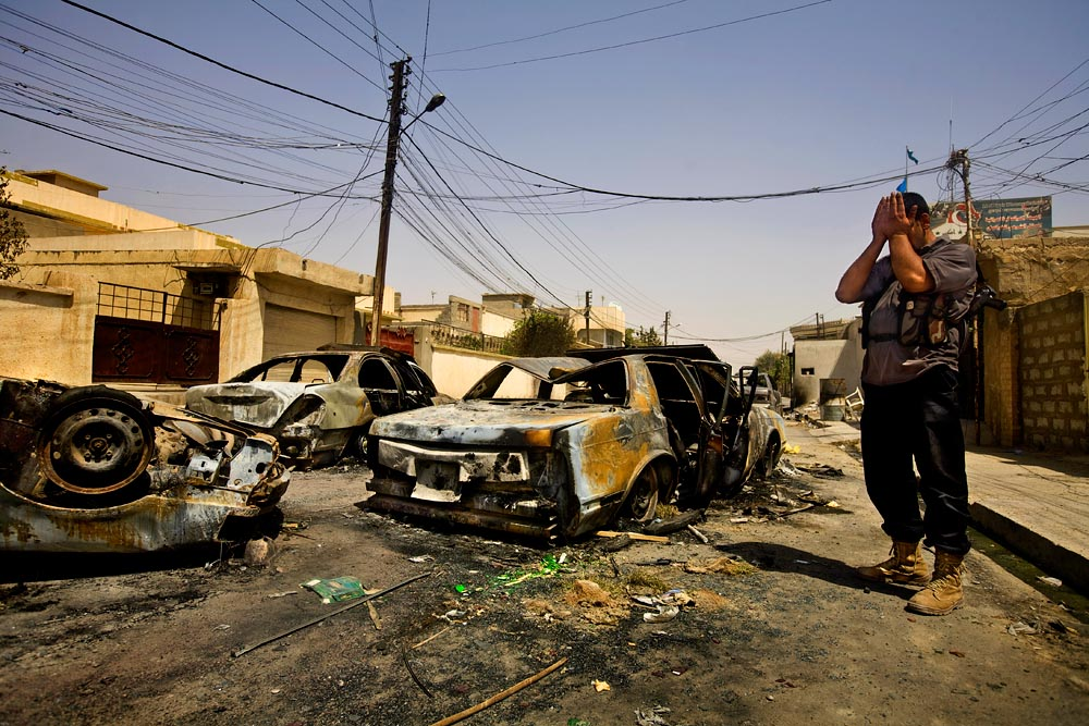A Turkish guard holds his head in his hands while surveying the burned remains of cars parked outside the Turkomen political offices in Kirkuk.