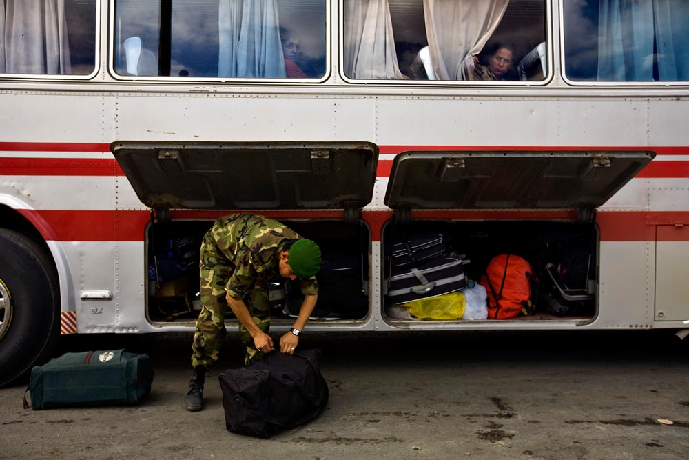 A Kurdish Asiash border soldier checks the luggage from an Iraqi civilian passenger bus entering Sulaimaniya.
