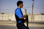 Iraqi Kurdish policemen, under the apparent control of a plain-clothed Asiash officer, patrols the streets in Kirkuk.