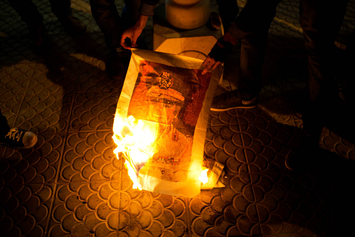 A crowd of Libyans burn a photograph of Muammar Gaddafi.