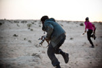 Libyan rebels run across the open plain of the desert during a battle with pro-Gaddafi forces.