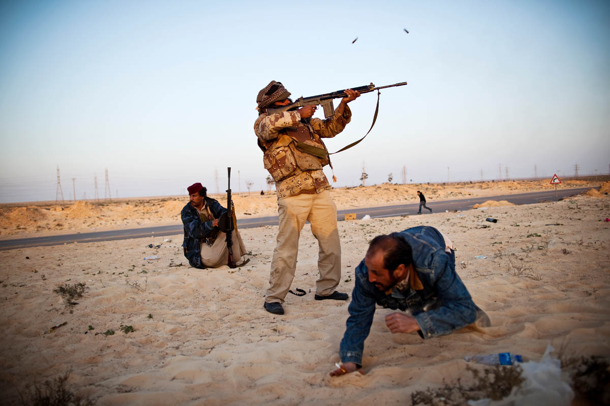 A civilian takes cover as a Libyan rebel fires towards Gaddafi loyalist forces on the outskirts of Ajdabiya.