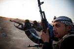 Libyan rebels take cover from behind a sand berm as pro-Gaddafi forces shell their position.