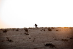 A Libyan rebel armed with an RPG, runs across the open desert during a battle with Gaddafi loyalist forces.